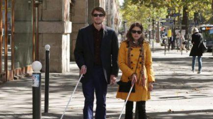 Deux personnes se promenent dans la rue avec une cane blanche