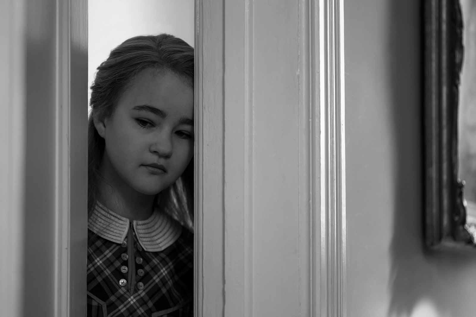 Photo tirée du film Wonderstruck, l'actrice Miilicent Simmonds se tient dans l'angle d'une porte