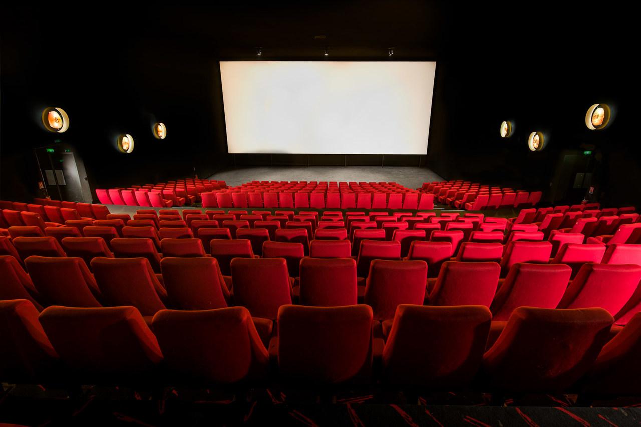 Une série de fauteuils en velours rouge sont alignés en quinconce et convergent vers un large écran blanc qui se découpe sur un fond noir. Deux hublots de part et d'autre de l'écran ponctuent les murs sombres.