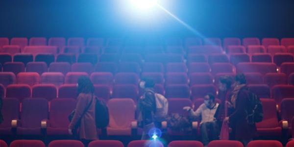 Sur l'image, les participants à l'atelier prennent place dans la salle de cinéma